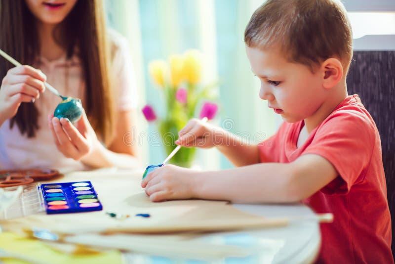 Les enfants ont peint des oeufs de pâques à la table photos stock