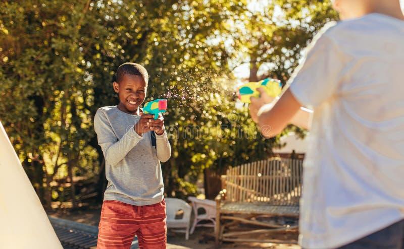 Les enfants a plaisir à jouer avec injectent des armes à feu dehors photos stock