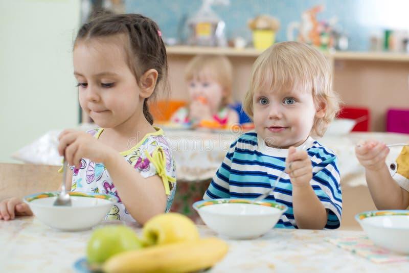Les enfants prennent le déjeuner au centre de jardin d'enfants ou de soins de jour photographie stock libre de droits