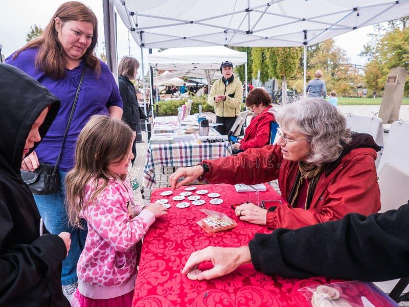 Les enfants reçoivent des timbres et des marques de main de jour de nourriture des volontaires images stock