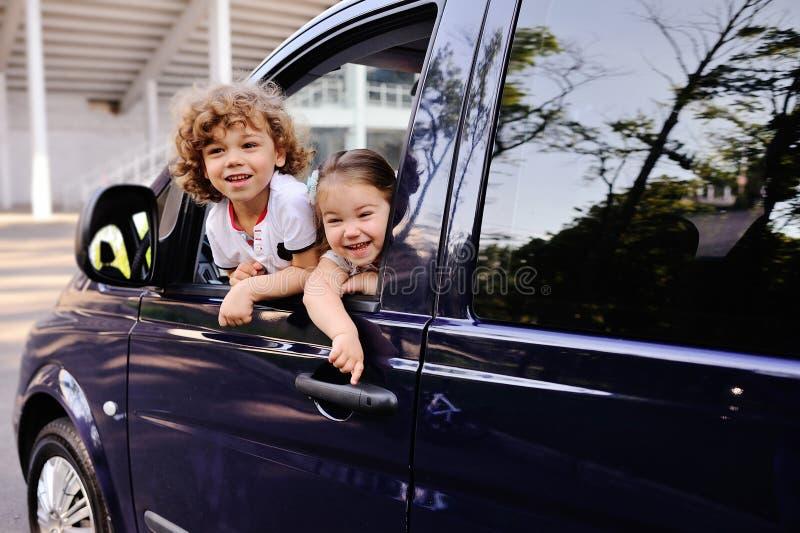Les enfants regardent d'une fenêtre de voiture photo libre de droits