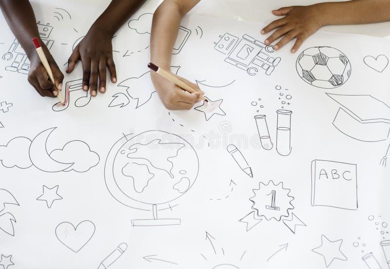 Les enfants remet tenir les crayons colorés peignant sur le papier de dessin d'art images libres de droits
