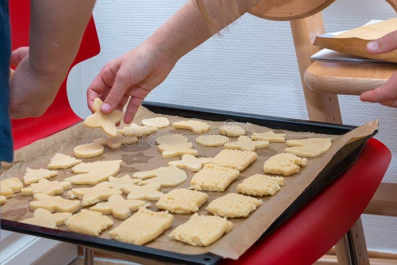 Les enfants remettent étendre le biscuit sur un plateau de cuisson photo libre de droits