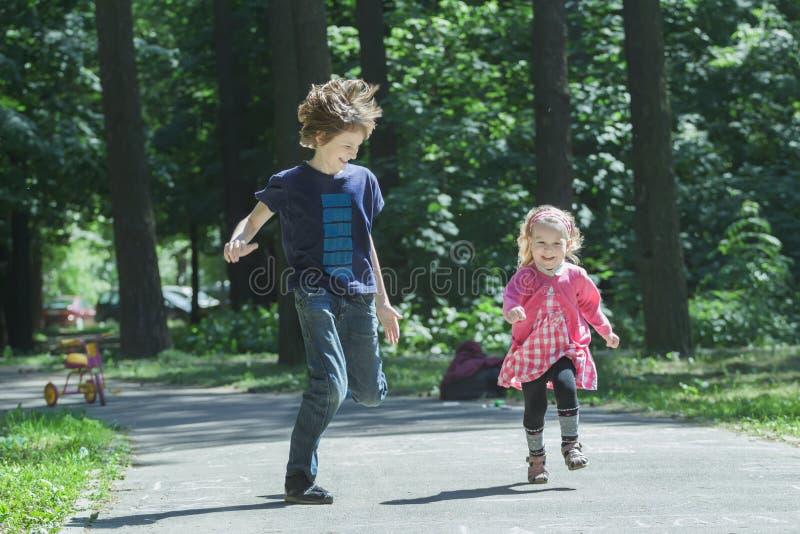 Les enfants riants d'enfant de mêmes parents jouant l'étiquette et le fonctionnement sur le parc asphaltent le sentier piéton photos libres de droits