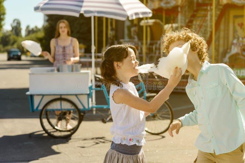Les enfants riants mangent la sucrerie de coton image libre de droits