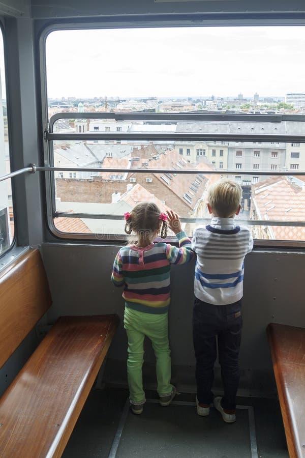 les enfants s'élèvent dans un funiculaire et un regard vides au panorama de la ville de Zagreb photos stock