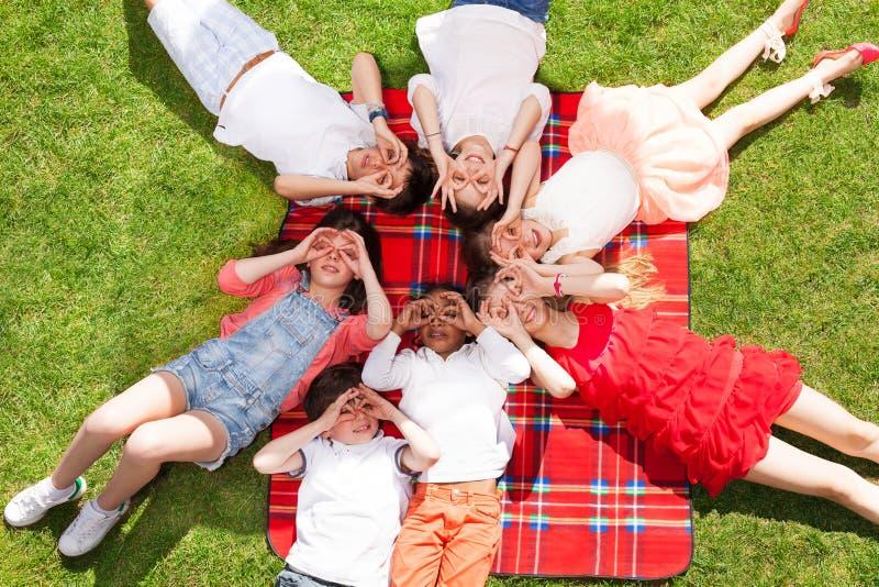 Les enfants s'étendant sur l'herbe et faisant des verres font des gestes images stock
