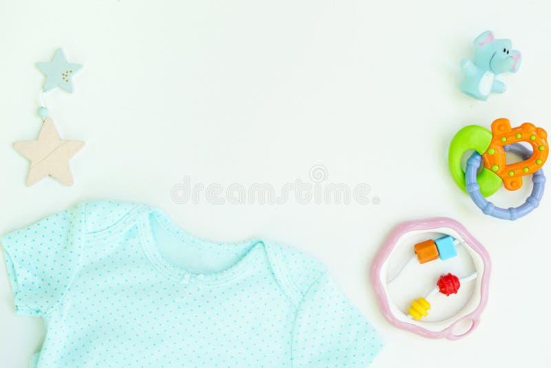 Les enfants s'allongent à plat avec des vêtements et des jouets en arrière-plan blanc en arrière-plan espace pour le texte photographie stock
