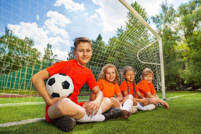 Les enfants s'asseyent dans la rangée près du boisage avec le football photo stock
