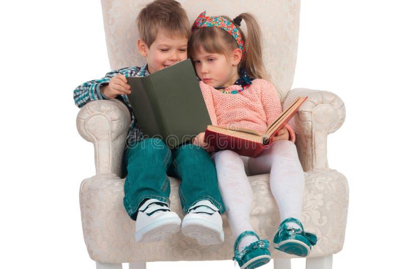 Les enfants s'asseyent dans une chaise avec des livres photo libre de droits