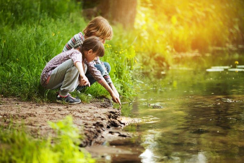 Les enfants s'asseyent près de l'eau photos stock
