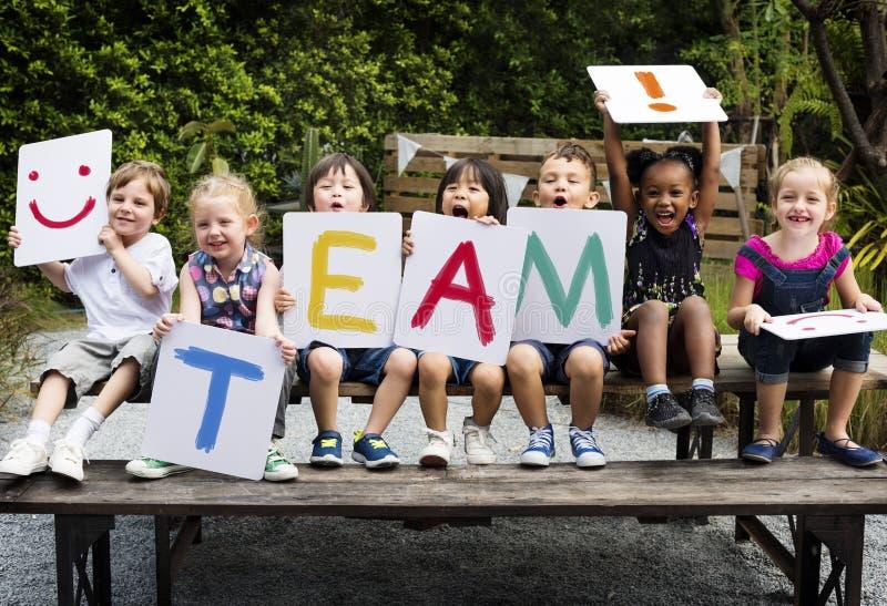 Les enfants s'asseyent sur la table en bois tenant une équipe de mot images libres de droits