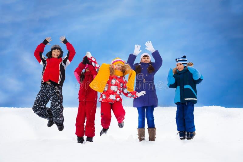 Les enfants sautant dans la neige photo libre de droits