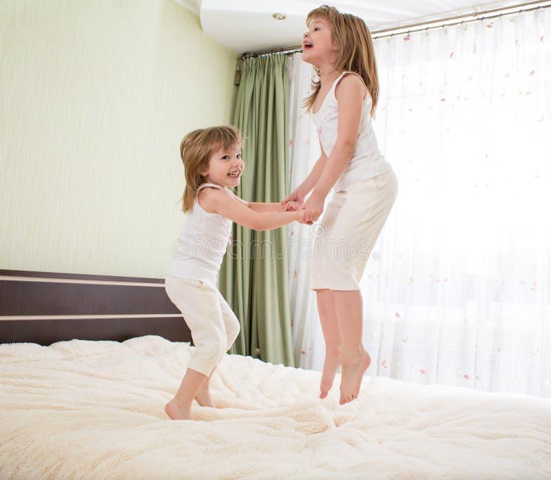 Les enfants sautant sur le lit photo stock