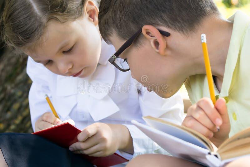 Les enfants se préparent aux examens se reposant dehors par temps beau après classe photo libre de droits