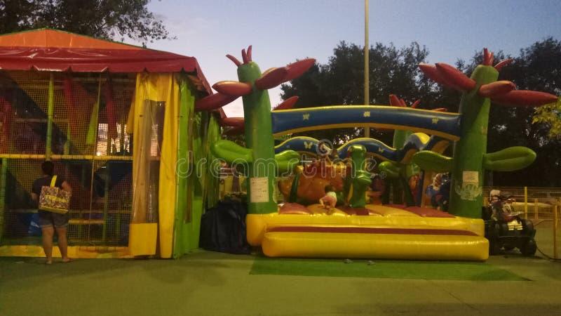 Les enfants se reposent en parc d'attractions sur le trempoline gonflable et labyrinthe au temps de début de soirée photo stock