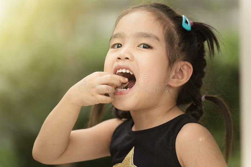 Les enfants se sentent heureux mangeant la sucrerie image libre de droits