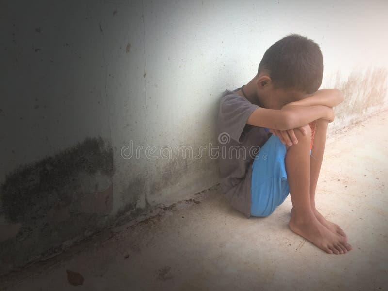 Les enfants se sont assis avec ses genoux pleurant contre le mur photographie stock libre de droits