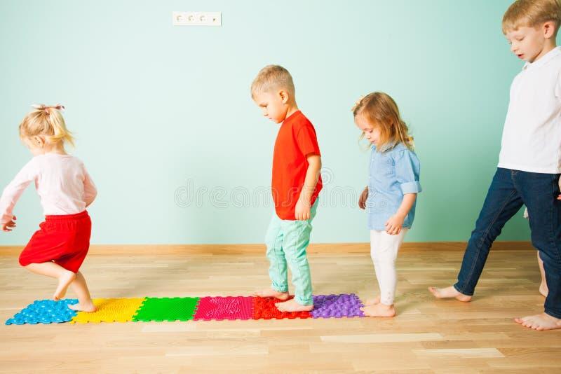 Les enfants se tiennent nu-pieds dans une rangée entre les tapis de massage photos libres de droits