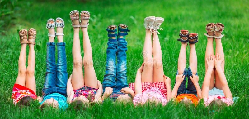 Les enfants se trouvant sur l'herbe verte en parc un jour d'?t? avec leurs jambes se sont soulev?s jusqu'au ciel photographie stock libre de droits