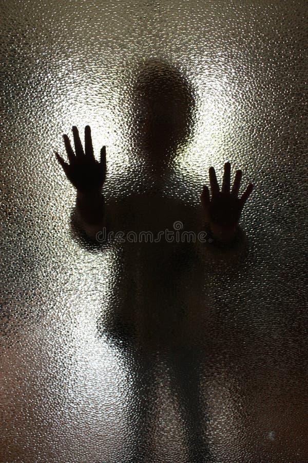 Les enfants silhouettent derrière une porte en verre photographie stock