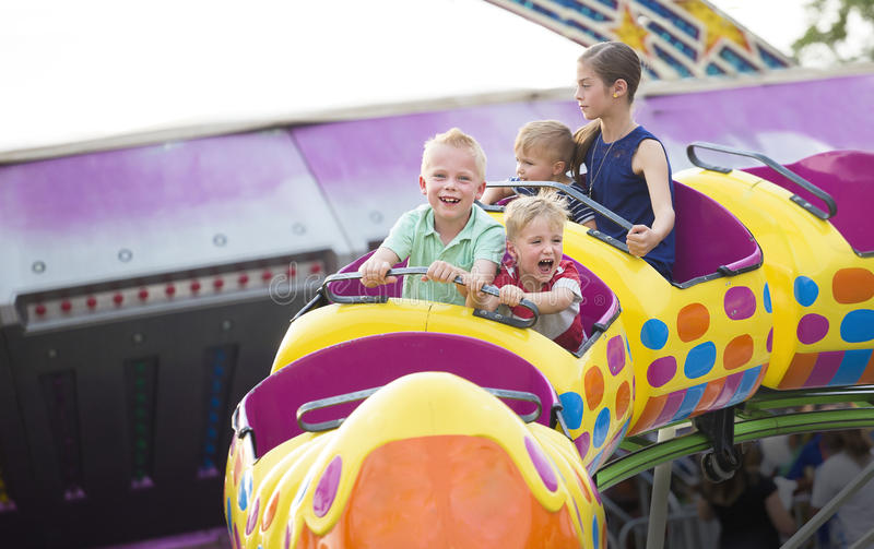Les enfants sur des montagnes russes excitantes montent à un parc d'attractions images libres de droits