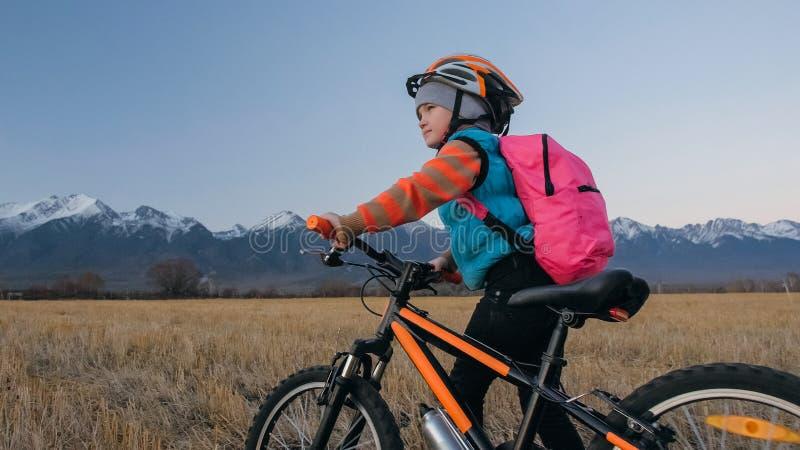 Les enfants un caucasiens marchent avec le vélo dans le domaine de blé Petite fille marchant le cycle orange noir sur le fond de  photographie stock libre de droits