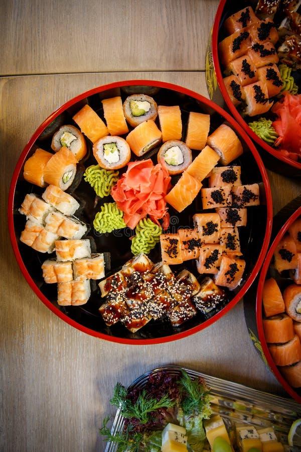 Les ensembles de nigiri, de petits pains et de sashimi de sushi ont servi dans le plat rond de Sushioke de noir traditionnel du J photographie stock libre de droits