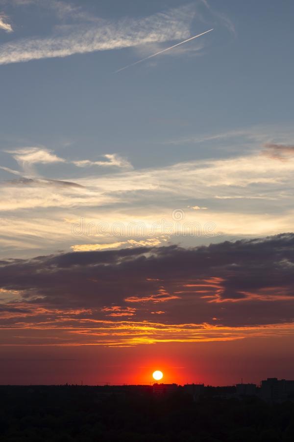 Les ensembles roses du soleil au-dessus de l'horizon de ville photographie stock