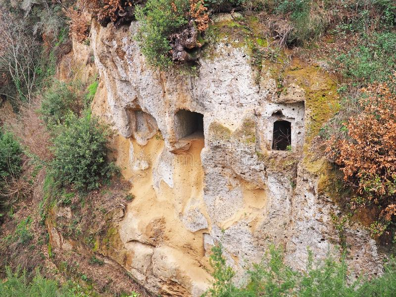 Les entrées de tombe dans le mur de falaise d'a par l'intermédiaire de cave, une route antique d'Etruscan ont découpé par des fal photographie stock