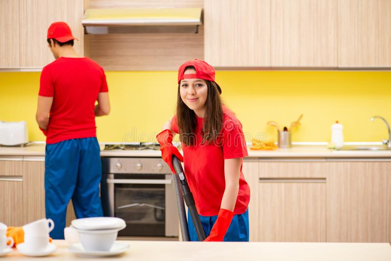Les entrepreneurs professionnels de nettoyage fonctionnant à la cuisine photographie stock