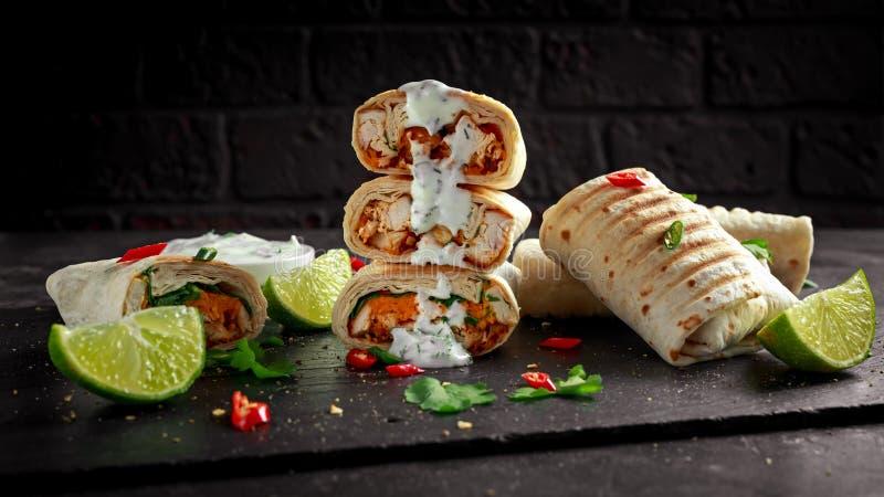Les enveloppes grillées saines de poulet et de persil, chargées avec du fromage, ont servi avec du yaourt grec profond, des pimen photographie stock