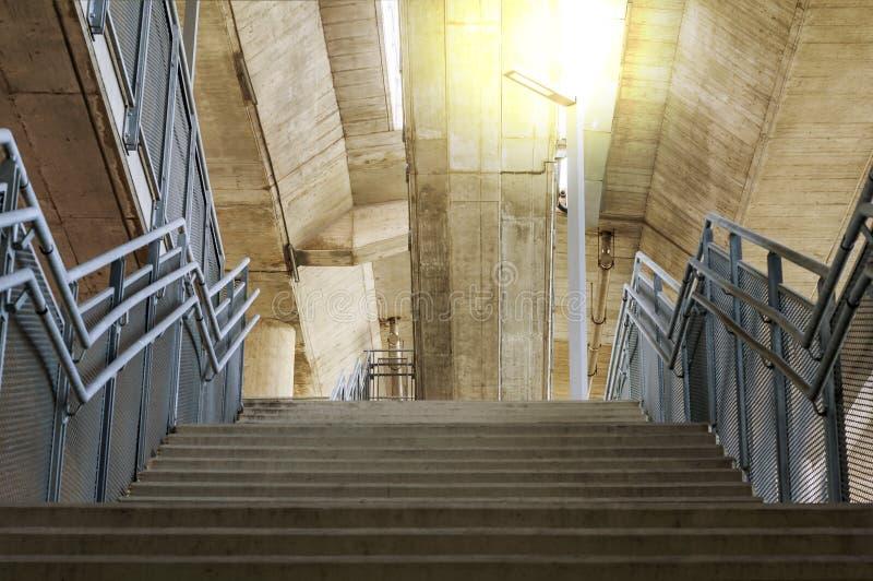 Les escaliers concrets sont des balustrades en métal sous le pont avec l'orange photo stock
