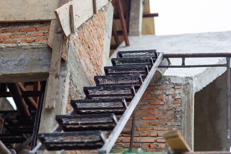 Les escaliers de fer ont placé avec des étapes modelées sur le vieux fond de brique photo stock