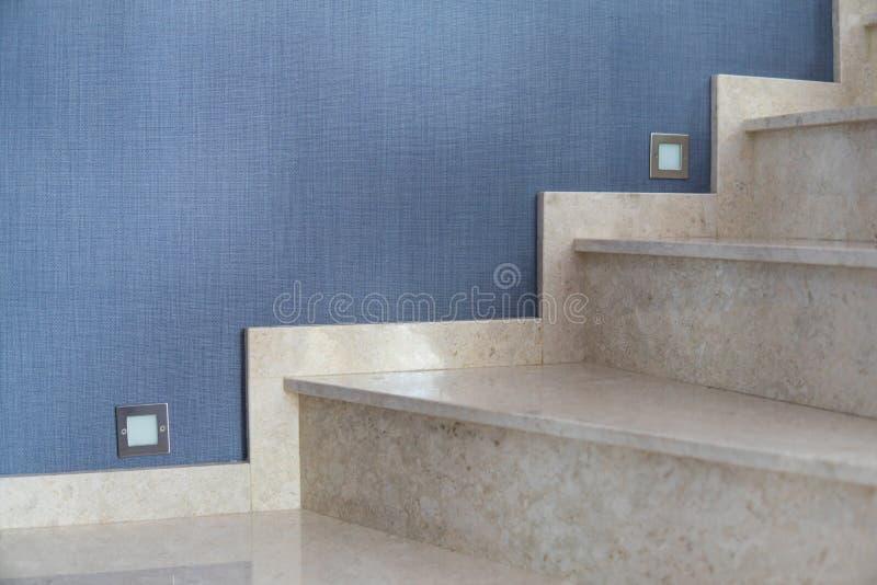 Les escaliers de marbre d'intérieur avec le fond bleu de papier peint et les escaliers s'allument image stock