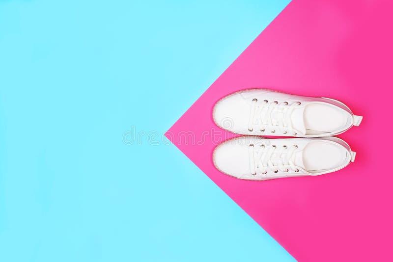 Les espadrilles blanches se trouvent sur le fond rose bleu de couleur au néon lumineuse photo stock