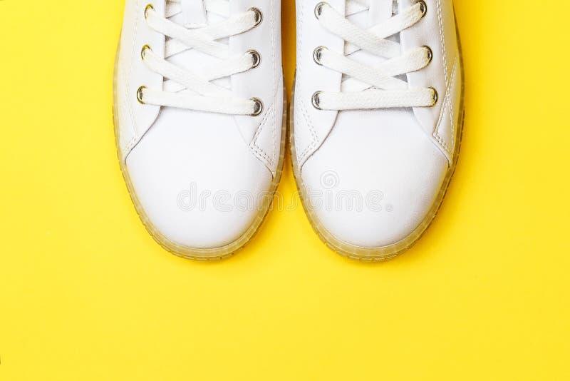Les espadrilles blanches se trouvent sur un fond jaune en pastel image stock