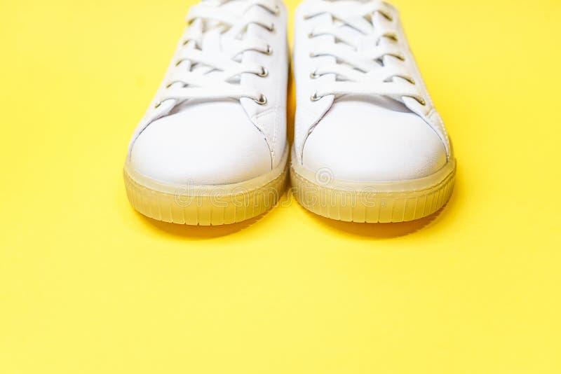 Les espadrilles blanches se trouvent sur un fond jaune lumineux images libres de droits
