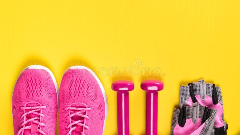 Les espadrilles, les gants et les haltères roses se situent dans une rangée sur un fond jaune, un endroit pour une inscription image stock