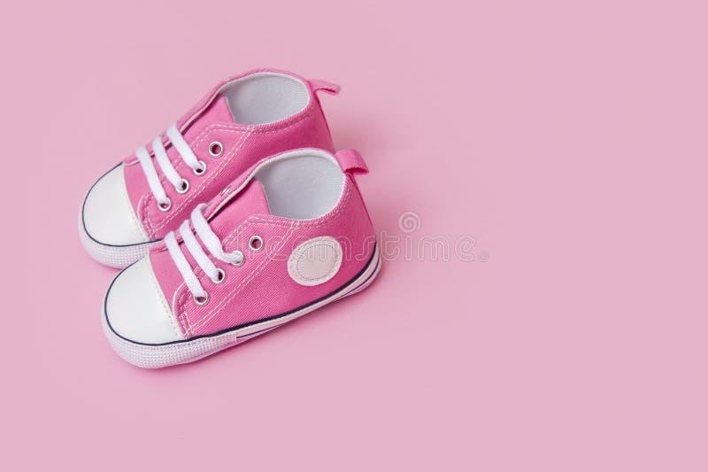 Les espadrilles roses mignonnes de bébé se ferment sur le fond rose photo libre de droits