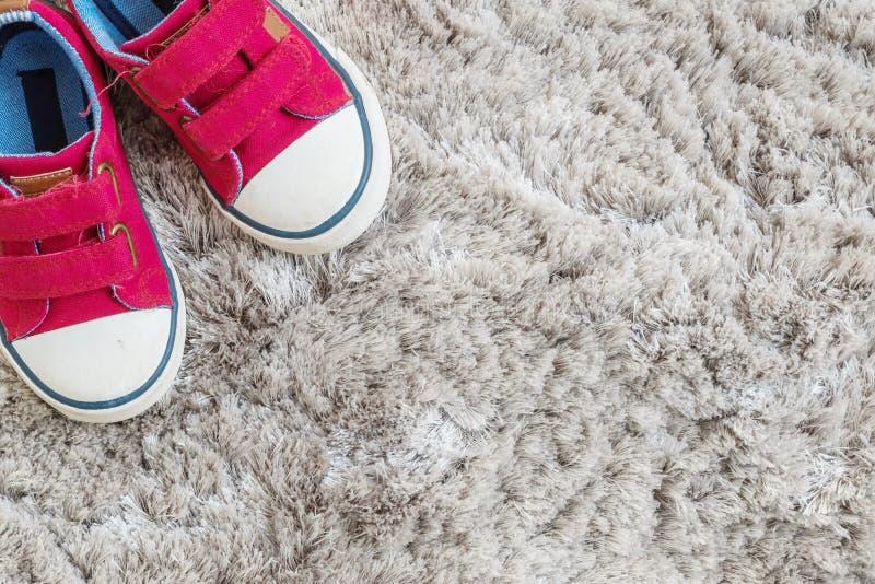 Les espadrilles rouges de tissu de plan rapproché de l'enfant sur le tapis gris ont donné au fond une consistance rugueuse dans l image libre de droits