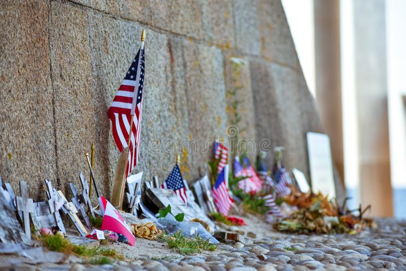 Les Etats-Unis et les drapeaux, les fleurs et les objets canadiens à la mémoire de tomber dans l'atterrissage de la Normandie photo stock