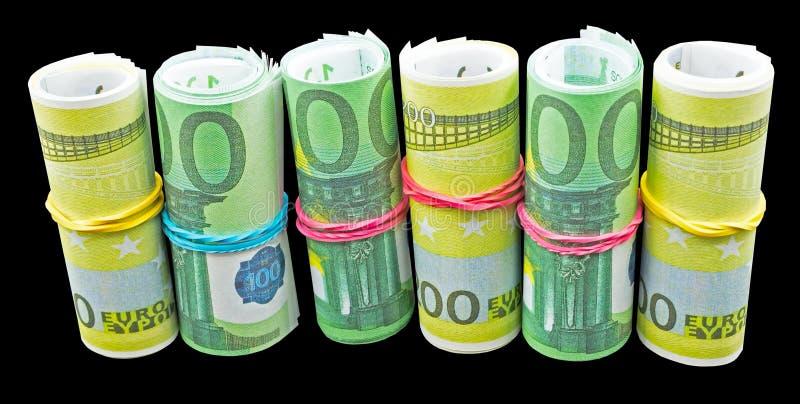 Les euro billets de banque d'argent roulent sur un noir image stock