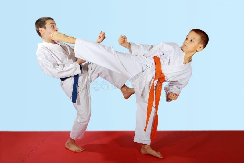 Les exercices appareillés ont exécuté par des athlètes avec la ceinture bleue et orange photos libres de droits