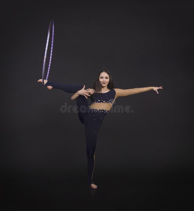 Les exercices gymnastiques avec la fille de cercle de danse polynésienne exécute un artiste de cirque image stock