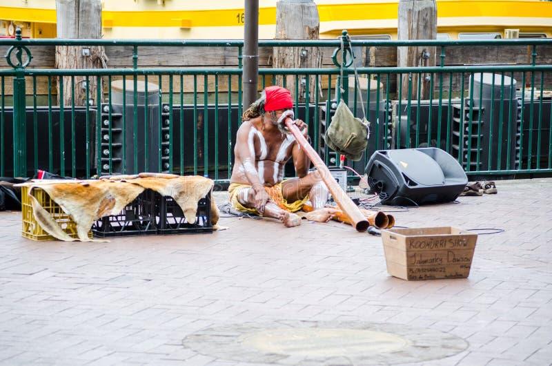 Les expositions australiennes indigènes de rue de musicien jouant le ` de Didgeridoo de ` est un instrument de vent développé par image stock