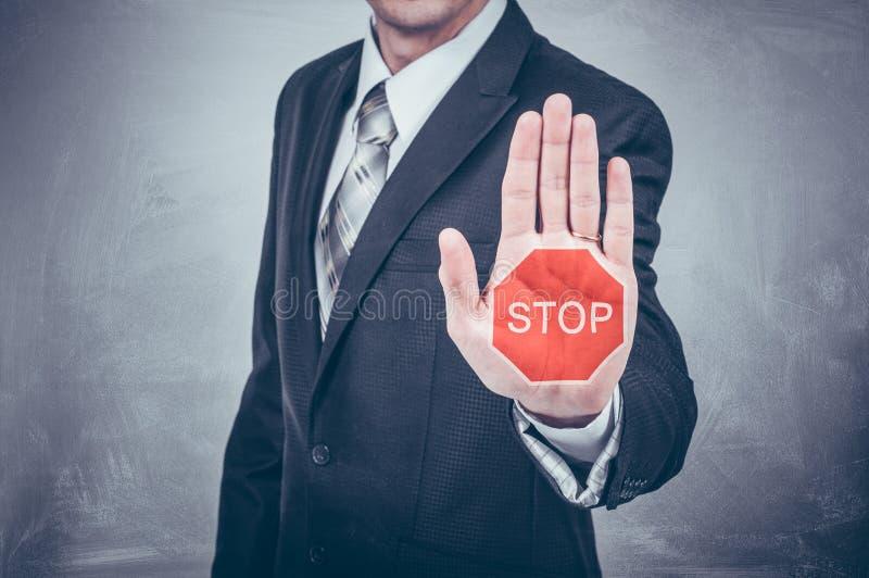 Les expositions d'homme d'affaires arrêtent le signe peint sur la main images libres de droits