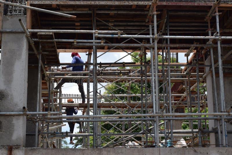 Les fabricants d'acier de construction de bâtiments travaillant par une maille d'échafaudage siffle au chantier photos libres de droits