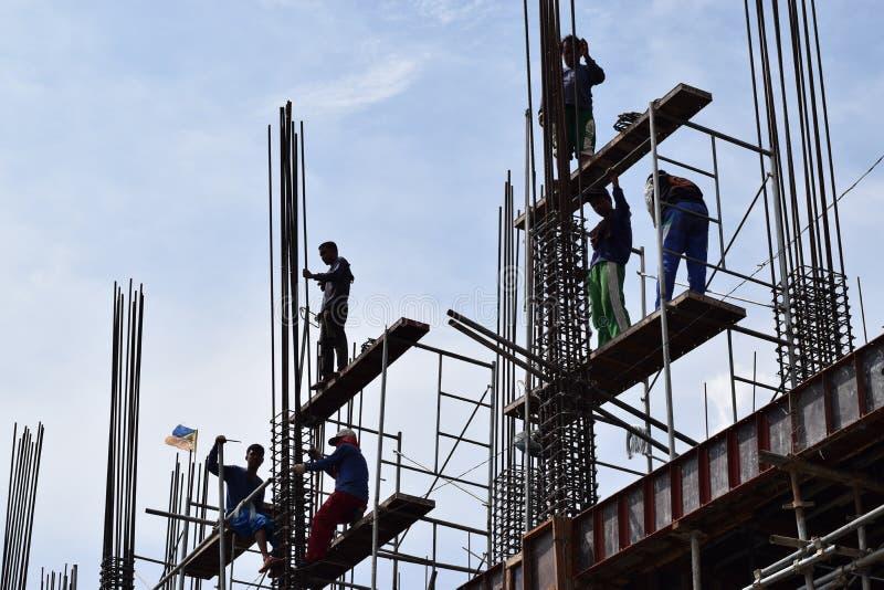 Les fabricants d'acier philippins de construction travaillant les morceaux en acier de jointure de colonne à bord de l'échafaudag images libres de droits