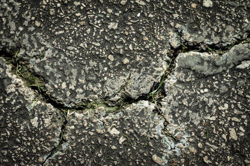 Les failles et les défauts donnent à la faiblesse montrée par le trottoir criqué Imperfections et asphalte rugueux Roche images libres de droits